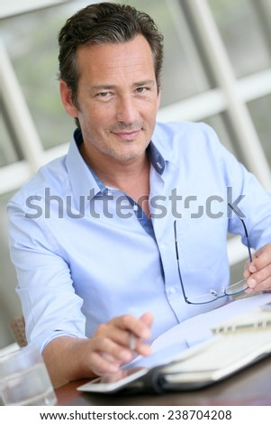 Portrait of businessman using digital tablet - stock photo