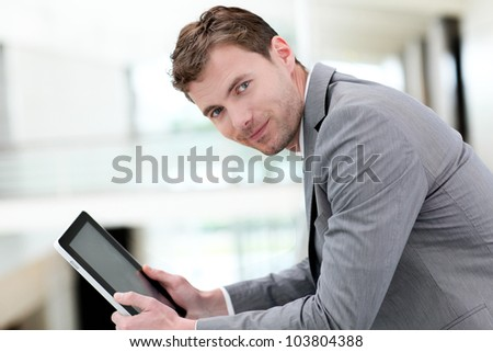 Portrait of businessman using electronic tablet in hall - stock photo