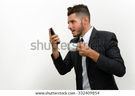 Portrait of businessman using phone and holding coffee cup