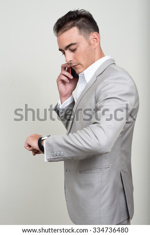 Portrait of businessman using phone and looking to his watch - stock photo
