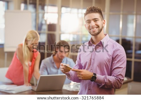 Portrait of businessman using phone in office with colleagues working in background - stock photo
