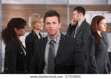 Portrait of businessman wearing grey suit, holding suitcase, standing in office lobby.? - stock photo