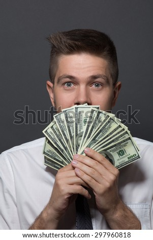 Portrait of businessman with dollars in his hands. Man with eyes like gimlet hiding behind roll of bank notes in the form of fan on dark grey.  - stock photo