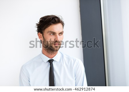 portrait of businessman with shirt and tie standing next to an office building window