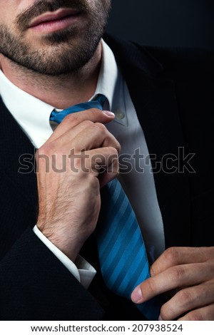 Portrait of businessman without face straightens tie himself. Isolated on black. - stock photo
