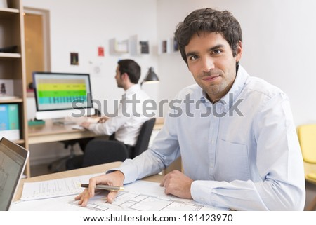 Portrait of Businessman working in office, looking camera