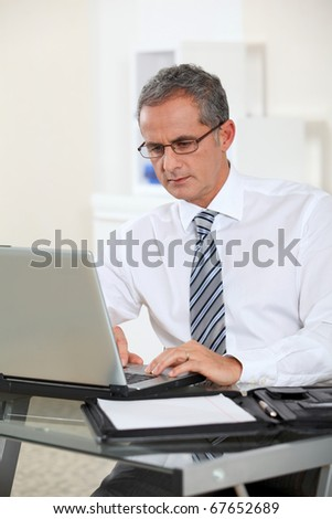Portrait of businessman working on laptop computer - stock photo