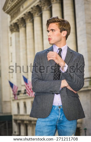 Portrait of Businessman. Young blonde, handsome graduate student, wearing blazer, necktie, jeans, standing by vintage style office building with American flags, looking away. Urban casual fashion. - stock photo