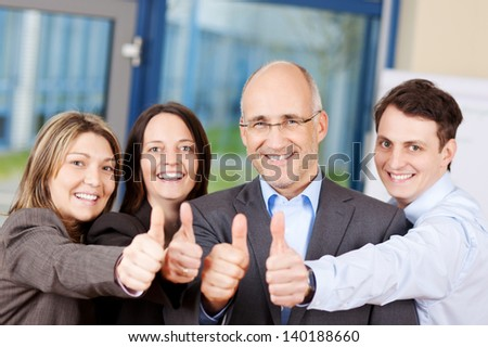 Portrait of businessmen and businesswomen showing thumbs up sign