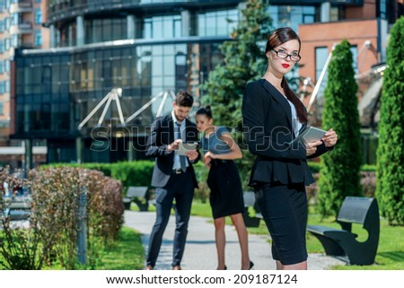 Portrait of businessmen. Confident and successful woman holds a plate and stands outside the office. On background are businessmen
