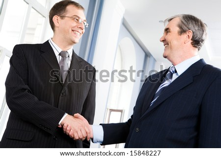 Portrait of businessmen shaking hands greeting each other in the corridor - stock photo