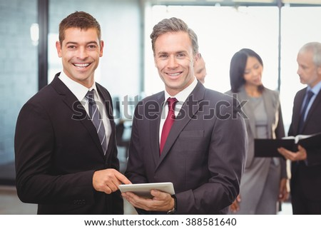 Portrait of businessmen using digital tablet in office