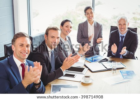 Portrait of businesspeople applauding in conference room during meeting - stock photo