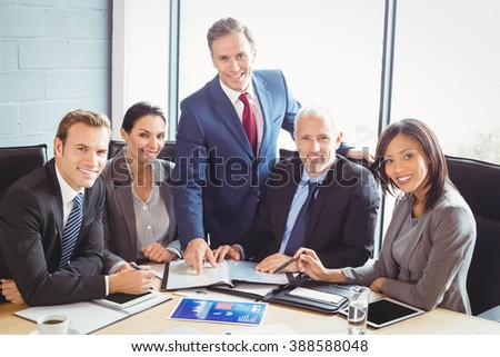 Portrait of businesspeople interacting in conference room during meeting