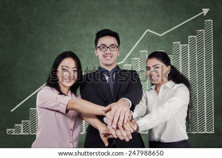 Portrait of businesspeople joining hands while smiling at the camera in front of business chart - stock photo