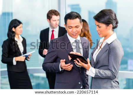 Portrait of businesspeople looking at tablet together - stock photo