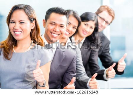 Portrait of businesspeople showing thumbs up