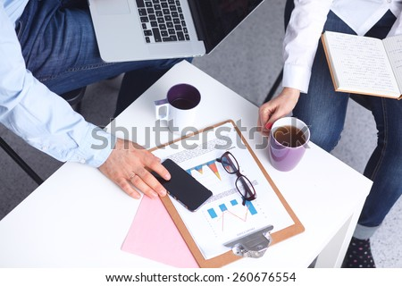 Portrait of  businesspeople sitting at  desk with a laptop