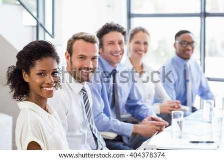 Portrait of businesspeople sitting together in meeting at office - stock photo