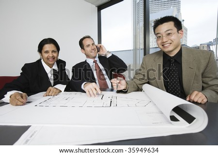 Portrait of businesspeople smiling in an office meeting.