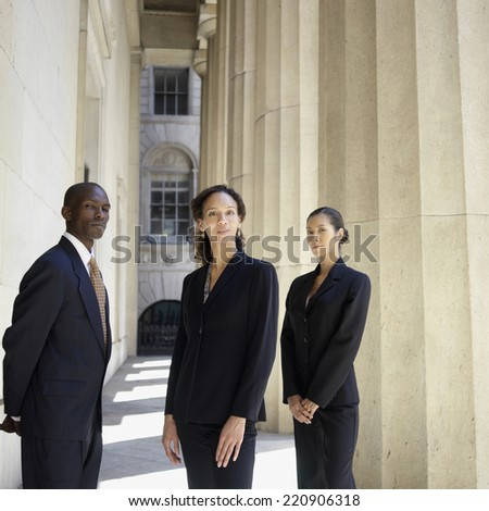 Portrait of businesspeople standing next to columns - stock photo