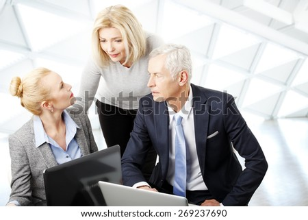 Portrait of businesswoman and businessman sitting in front of computer while sales woman standing in background. Business team working on presentation at office.  - stock photo