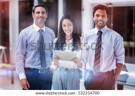 Portrait of businesswoman and businessmen with digital tablet in office