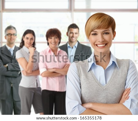 Portrait of businesswoman and team of happy businesspeople.
