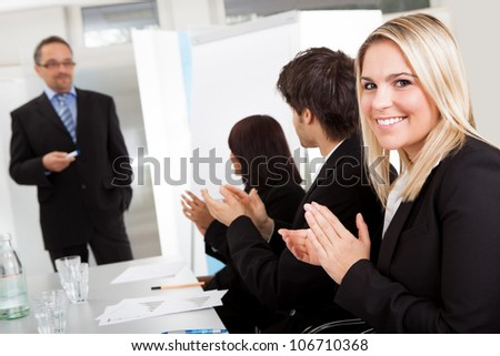 Portrait of businesswoman at presentation applauding to the lecturer - stock photo