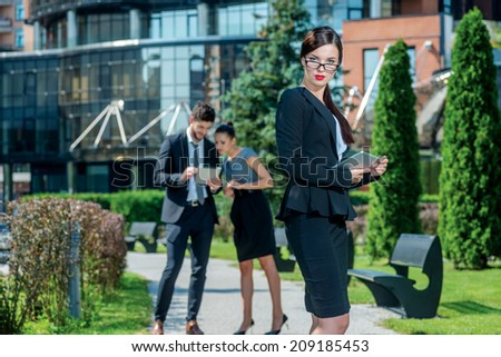 Portrait of businesswoman. Confident and successful woman holds a plate and stands outside the office and looks straight into the camera. On the background of businessmen are doing business