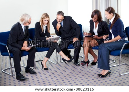 Portrait of businesswoman explaining work to her colleagues on a tablet at the office - stock photo