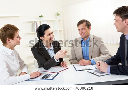Portrait of businesswoman explaining work to his colleagues in office