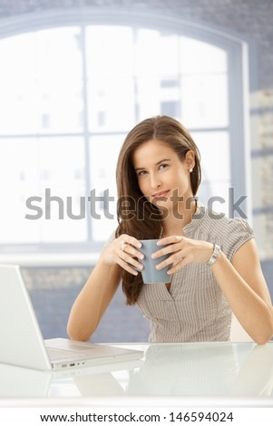Portrait of businesswoman having coffee, sitting at table with laptop computer, smiling at camera.