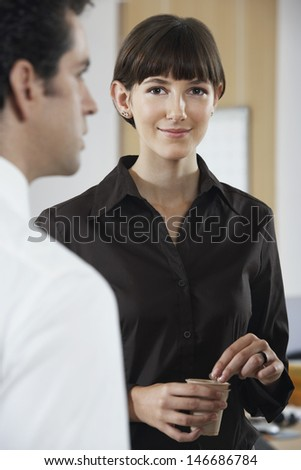 Portrait of businesswoman holding coffee cup while standing with colleague in office - stock photo