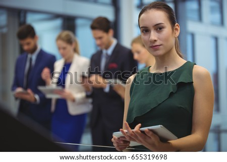 Portrait of businesswoman holding digital tablet at office