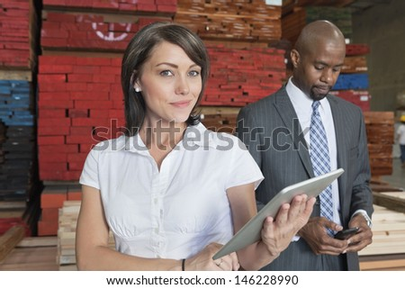 Portrait of businesswoman holding tablet PC while colleague using cell phone - stock photo