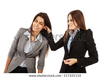 Portrait of businesswoman pulling colleague's ear isolated on white - stock photo