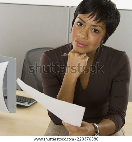 Portrait of businesswoman reading papers at desk - stock photo