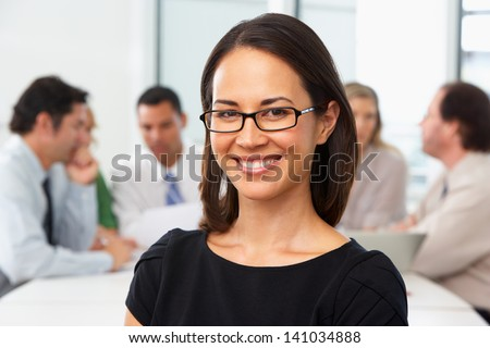 Portrait Of Businesswoman Sitting At Boardroom Table - stock photo