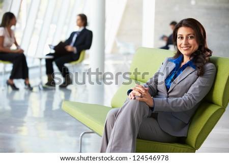 Portrait Of Businesswoman Sitting On Sofa In Modern Office - stock photo