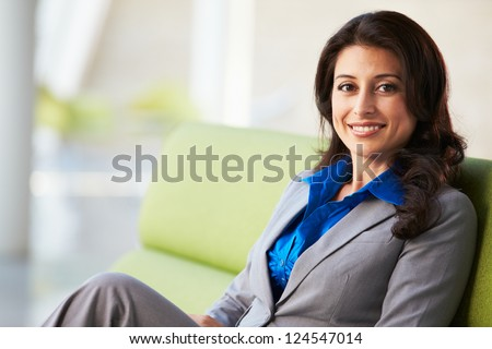 Portrait Of Businesswoman Sitting On Sofa In Modern Office - stock photo