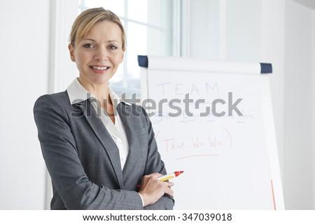 Portrait Of Businesswoman Standing By Flipchart - stock photo