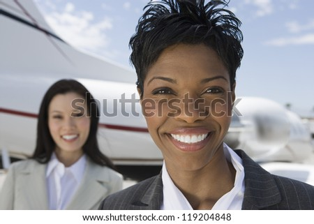 Portrait of businesswoman standing in front of private plane - stock photo