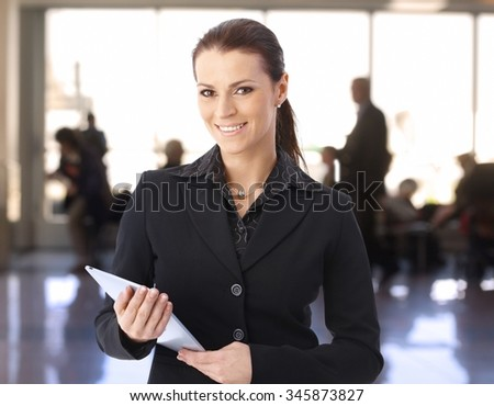 Portrait of businesswoman standing in lobby using tablet computer, looking at camera, smiling.