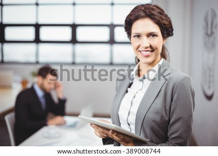 Portrait of businesswoman using tablet computer while colleague in background