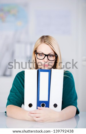 Portrait of businesswoman wearing glasses while holding white binders at office desk - stock photo
