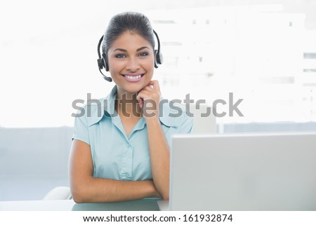 Portrait of businesswoman wearing headset in front of laptop in office