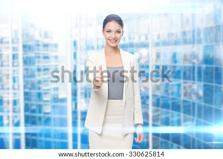 Portrait of businesswoman who thumbs up, modern blue background. Concept of leadership and success - stock photo