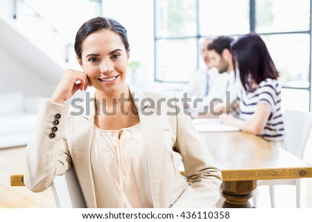 Portrait of businesswoman with her colleagues in background at office - stock photo