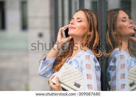 Portrait of businesswoman with her eyes closed. Pretty lady with long brown hair holding white little bag at her hand and talking over mobile phone. - stock photo